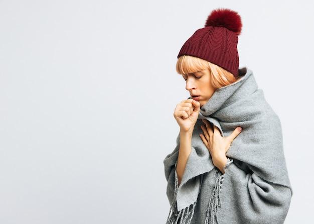Donna in cappello rosso che tossisce, occhi chiusi, isolati. stagione influenzale. copia spazio