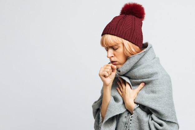 Donna con cappello rosso che tossisce, avvertendo i primi sintomi della malattia.bronchite, stagione influenzale