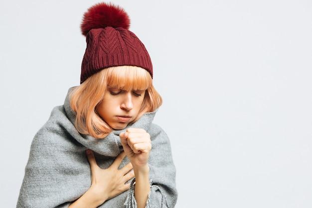 Donna con cappello rosso che tossisce, avvertendo i primi sintomi della malattia. broncite, influenza