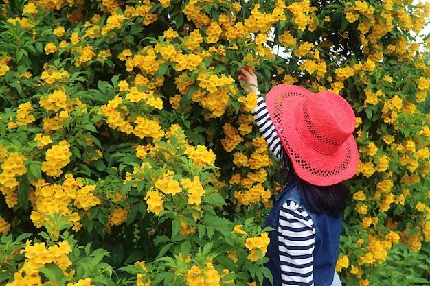Donna in red hat godetevi la bellezza dell'albero in fiore giallo trumpetbush