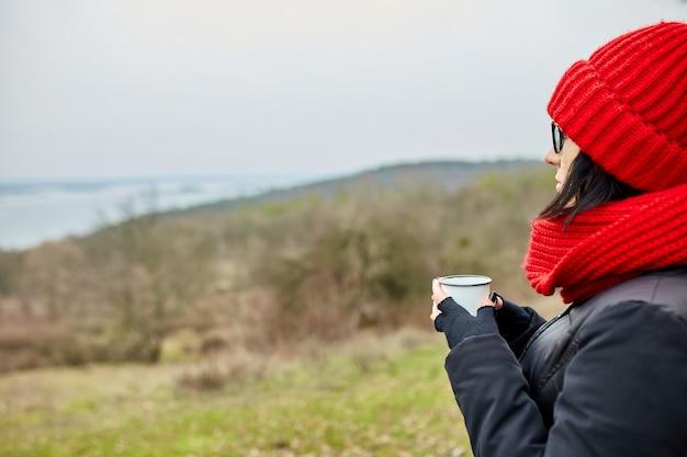 Donna con cappello rosso e sciarpa, bevendo tè da una tazza di metallo all'aperto, concetto di viaggio, paesaggio di sfondo autunnale.