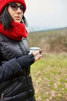 Donna con cappello e sciarpa rossi, bevendo tè da una tazza di metallo all'aperto