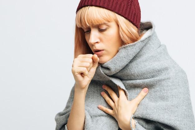 Donna con cappello rosso, avvolta in una calda sciarpa che tossisce, avvertendo i primi sintomi della malattia