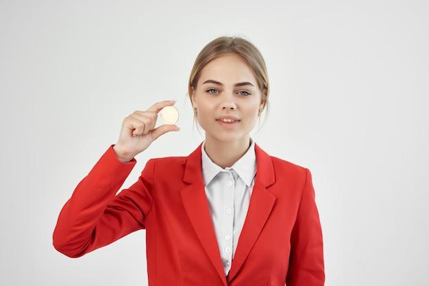 La donna in una giacca rossa con moneta d'oro bitcoin ha isolato lo sfondo