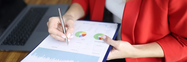 La donna in giacca rossa firma il documento negli appunti un tavolo con un collega in primo piano dell'ufficio. concetto di mercato di ricerche di mercato.