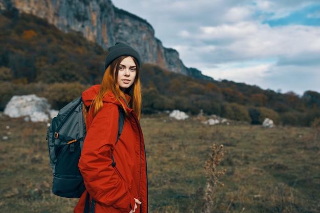 Una donna con una giacca rossa e cappelli caldi cammina in un prato in montagna nella natura. foto di alta qualità