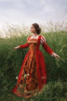 Donna in un abito rosso medievale in piedi nell'erba