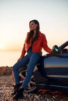 Donna in rosso vicino al cabriolet che indossa occhiali da sole