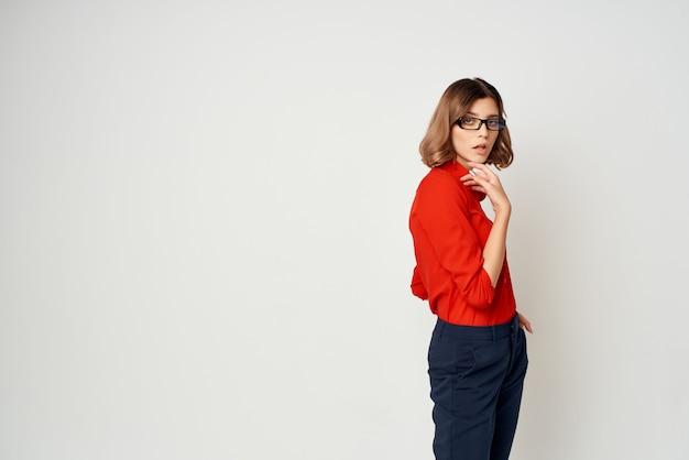 Donna in camicia rossa in posa sfondo chiaro ufficiale di moda fashion