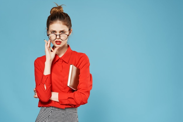 Donna in camicia rossa con blocco note e penna segretaria ufficio di lavoro. foto di alta qualità