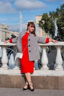 Una donna in rosso sta alla ringhiera del ponte della città. in cappotto e cappello.
