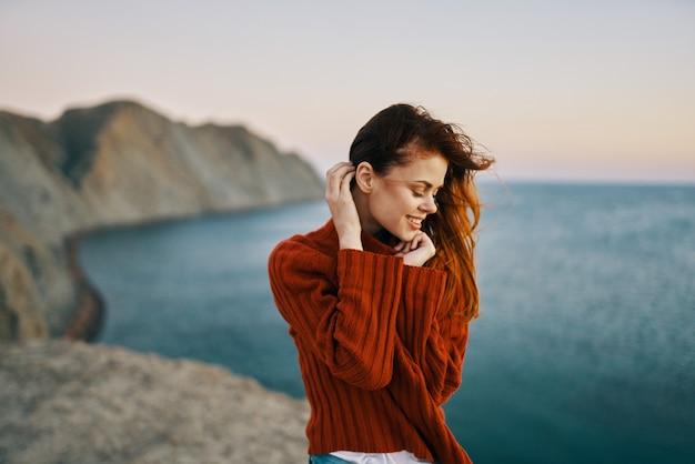 Donna in un maglione rosso in montagna vicino al modello di turismo di viaggio per mare. foto di alta qualità