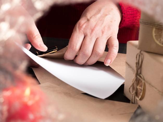 Una donna con un maglione rosso mette una lettera in una busta dietro un vetro ghiacciato.