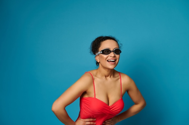 Donna in costume da bagno rosso e googles su sfondo blu