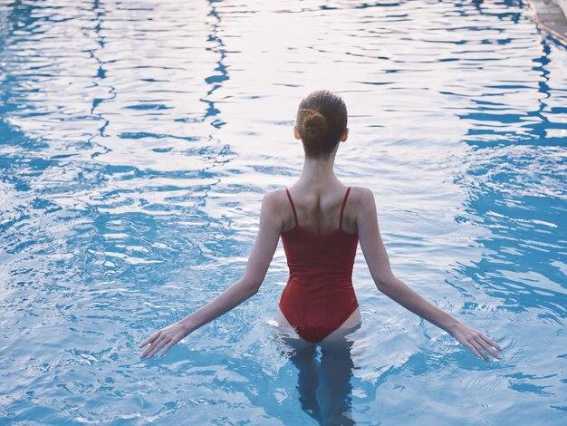 La donna in costume da bagno rosso fa scorrere le mani sull'acqua trasparente in piscina