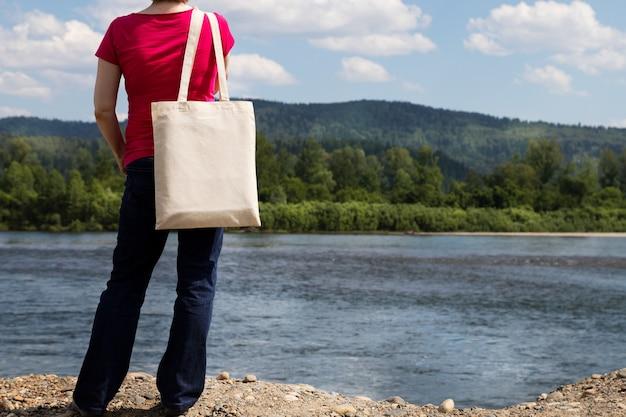Donna in maglietta rossa che trasporta il mockup vuoto riutilizzabile della borsa della spesa.