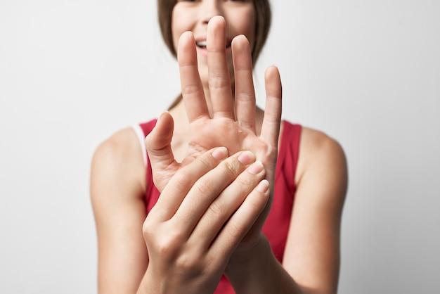 Donna in maglietta rossa per il trattamento della lesione del dolore articolare alla mano