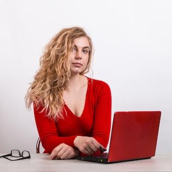 Donna in rosso, lavorando da remoto al computer su bianco.