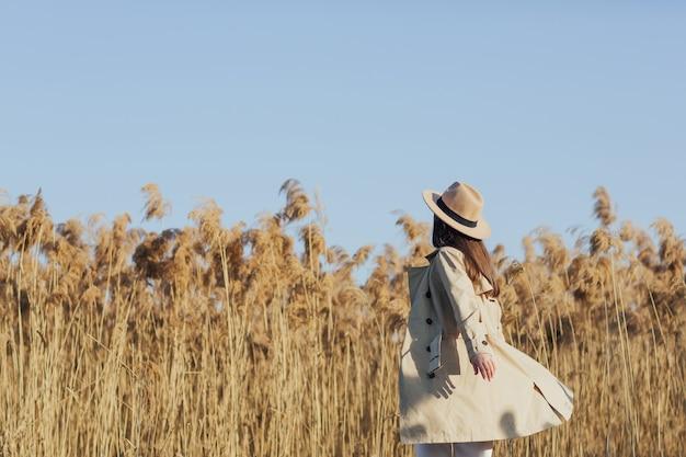 Donna nel campo di canne in una giornata di sole con cielo blu