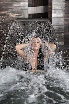 Donna rinfrescante in piscina con cascata