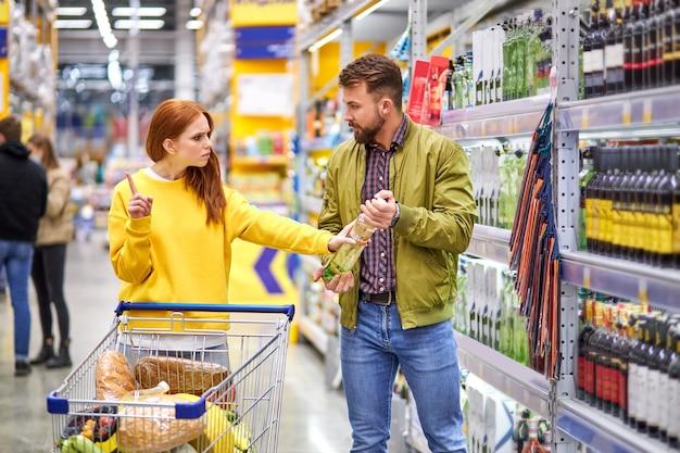 La donna rifiuta al marito di comprare alcolici, sta litigando nel negozio nel reparto alcol, shopping, concetto di alcol