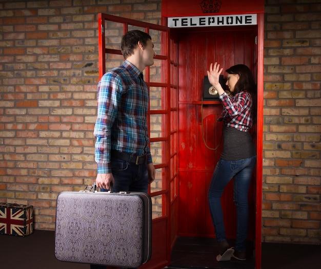 Donna che si rifiuta di ascoltare suo marito mentre la implora di chiudere il telefono in una cabina telefonica pubblica mentre lui ha un viaggio da fare con la sua valigia