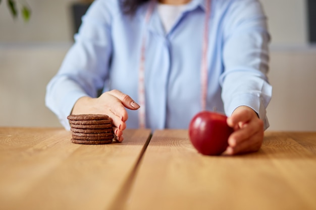 Donna che rifiuta cibo spazzatura o cibo malsano come biscotti o dessert e sceglie cibo sano