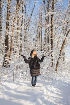 La donna esulta nella neve in inverno pineta con neve sugli alberi e sul pavimento in una giornata di sole. Foto Premium