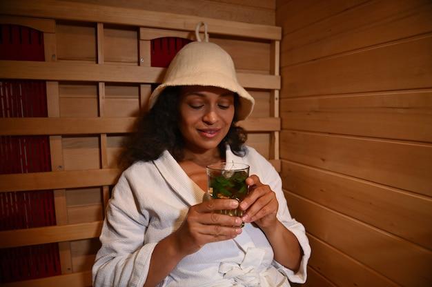 Una donna si rilassa in una sauna a infrarossi in legno e si gode una deliziosa e salutare bevanda vitaminica con frutti di bosco e foglie di menta. trattamento termale