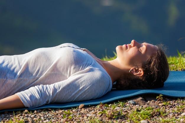 La donna si rilassa nell'asana savasana di yoga all'aperto
