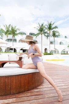 Donna che si distende in piscina con noci di cocco, vacanze estive.