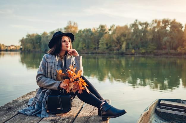 Donna che si rilassa sul molo del lago in barca ammirando il paesaggio autunnale al tramonto tenendo rami con foglie. attività per la stagione autunnale
