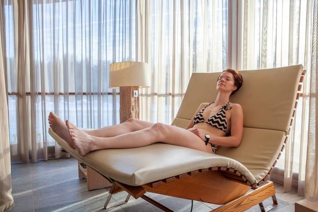 Donna che si distende su un lettino nel centro benessere.