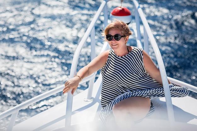 Donna che si rilassa sul naso dello yacht in una soleggiata giornata estiva in mare e si gode le vacanze e i viaggi di lusso