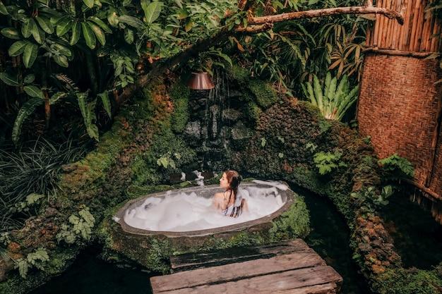 Donna che si rilassa nel bagno all'aperto con l'hotel di lusso della stazione termale della giungla tropicale