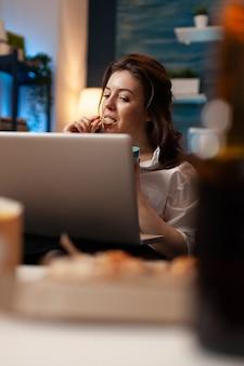 Donna che si rilassa sul divano mangia uno spuntino gustoso mentre guarda un film comico sul laptop