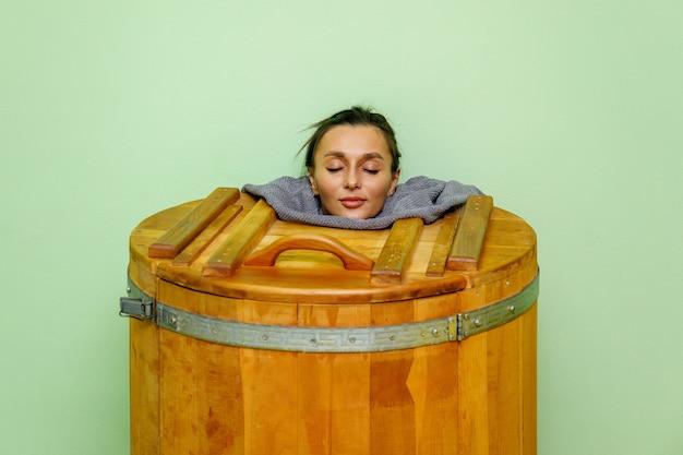 Donna che si distende nella vasca idromassaggio in legno spa, sauna a botte o vasca da bagno in cedro