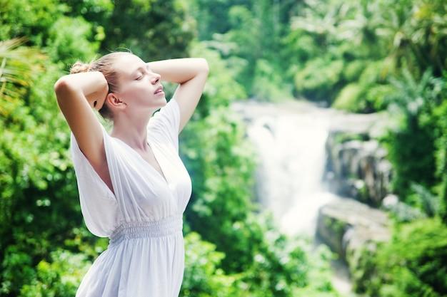 Donna che si rilassa con gli occhi chiusi davanti alla cascata
