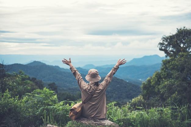 Donna che si distende con le braccia alzate sulla cima della montagna.