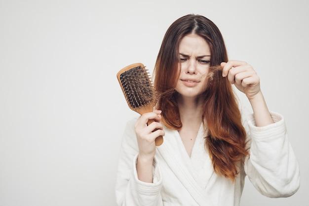 La donna rimuove i riccioli di capelli da un modello di perdita di problemi di salute del pettine
