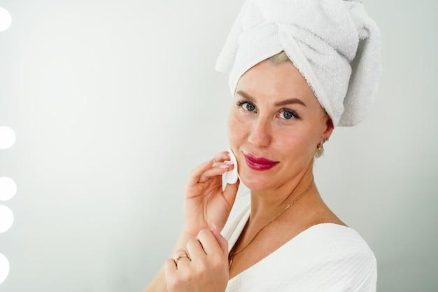 Una donna si strucca con un tovagliolo in bagno si pulisce il viso con un batuffolo di cotone detergente e...
