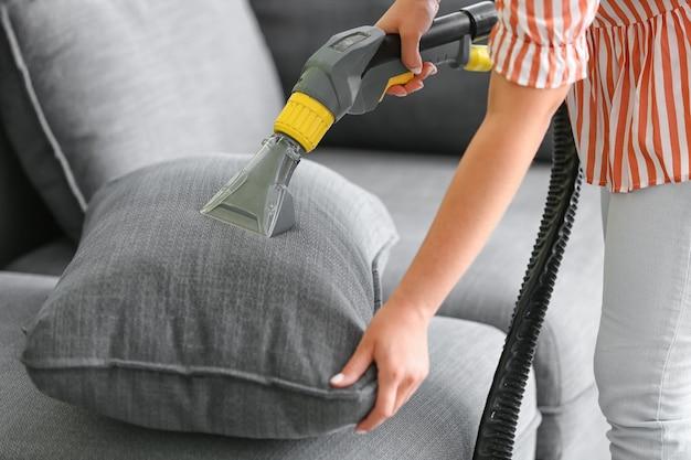 Donna che rimuove lo sporco dal divano di casa