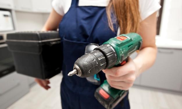 La donna riparatrice vestita in uniforme da lavoro in casa con un cacciavite e altre attrezzature in mano