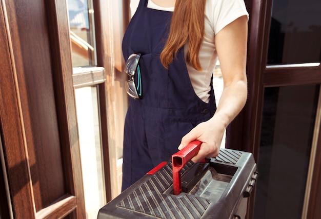 La donna riparatrice vestita in uniforme da lavoro sta entrando in casa con una cassetta degli attrezzi e altre attrezzature in mano