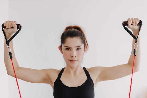La donna fa l'allenamento con la fascia di resistenza sulla parte superiore del torace nella sua camera da letto