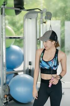 Riposo della donna dopo l'allenamento in palestra con la corda per saltare nel concetto di palestra, fitness e sport.