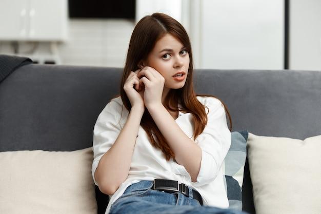 Donna che riposa in un appartamento seduto sul divano comfort.