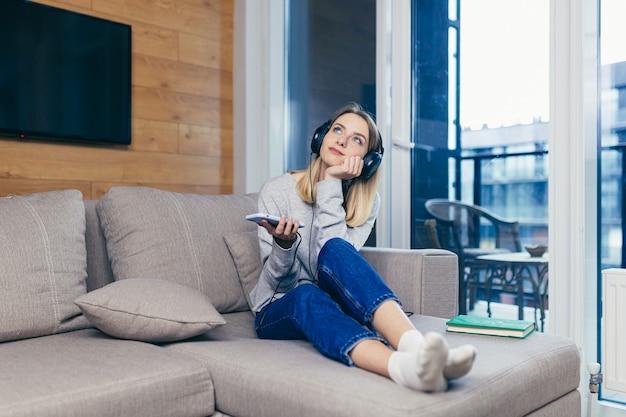 Donna che riposa a casa ascoltando podcast audio seduta sul divano usando le cuffie