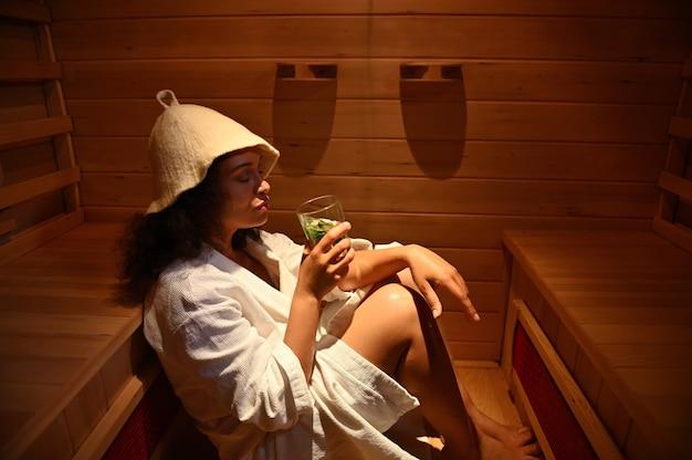 Donna che riposa nella sauna a infrarossi. trattamento termale resort. concetti di terapia di bellezza