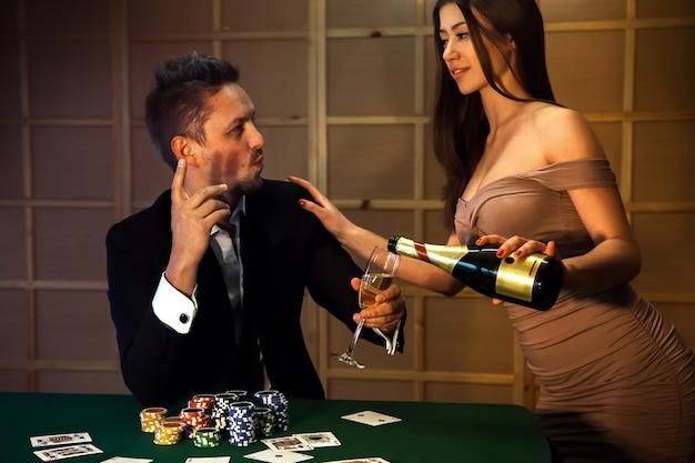 La donna in un vestito rivelatore con una scollatura profonda versa champagne poker playerñž a seconda del concetto di gioco d'azzardo e casinò